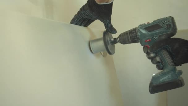 Close up, repairman makes a hole in the wall