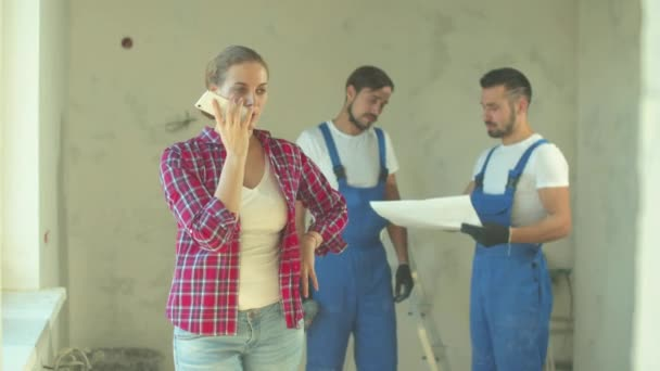 Woman records a voice message, repairmen stands on the background