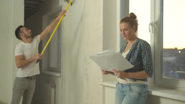 Man paints a wall, woman looks at drawings