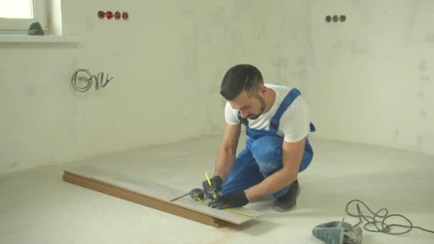 Repairman in uniform cuts a piece of a tile