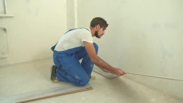 Builder in uniform puts laminate on the floor