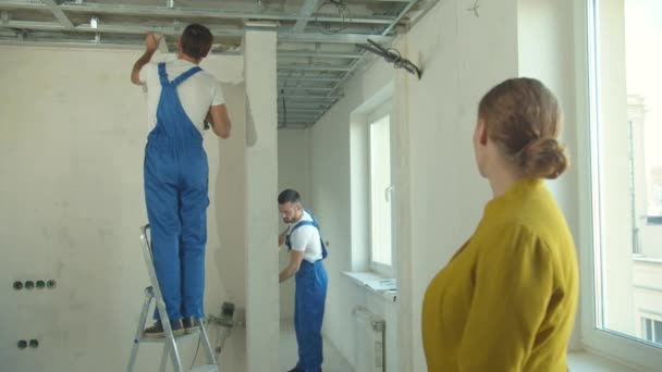 Woman watches how repairmen work in the flat