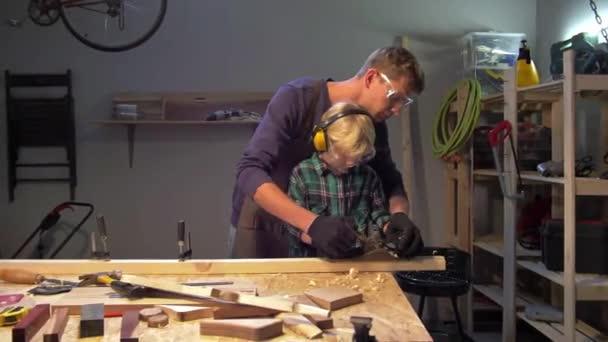 Mistr učí malého chlapce leštit dřevěnou desku