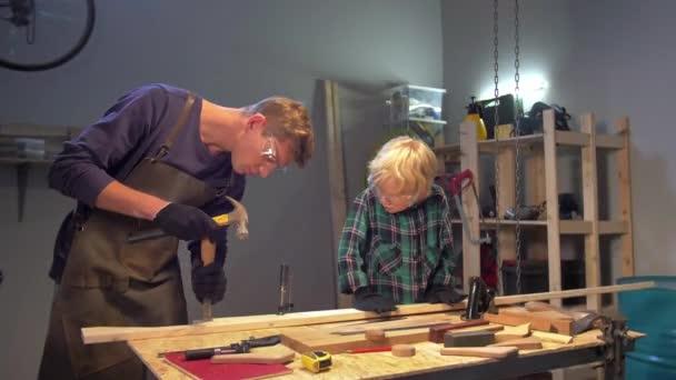 Muž ukazuje chlapci, jak pracovat se dřevem v dílně
