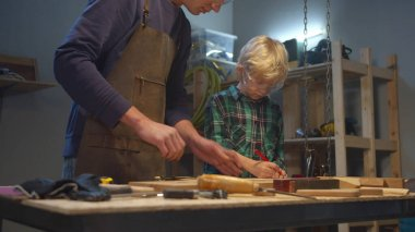 Dad teaches son to use work tools