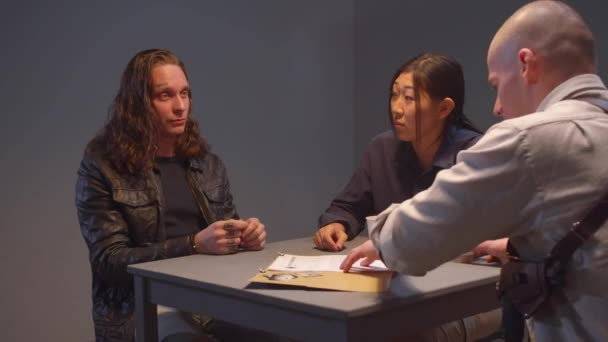 Two police officers and a criminal in an interrogation room