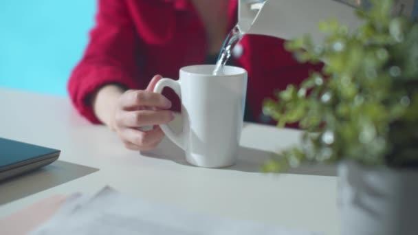 Pracovník z kanceláře nalévá vodu z konvice. Zpomalení