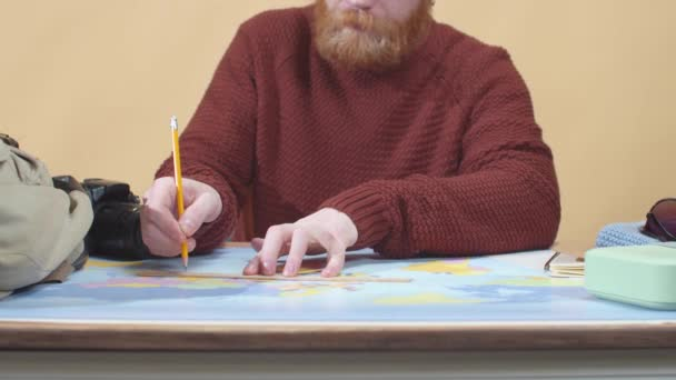 Bearded man in a sweater draws on a map