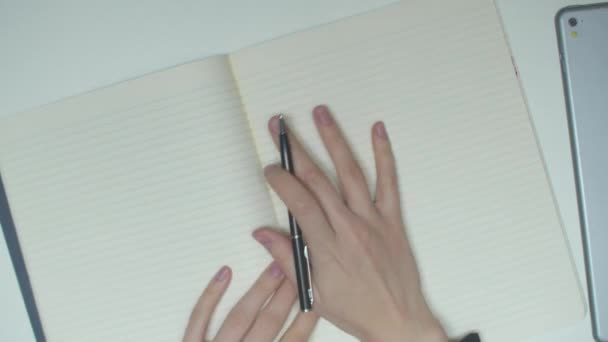 A student writes in a notebook. Top view