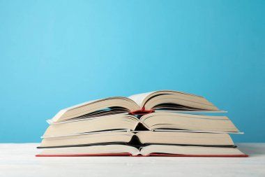 Stack of books against blue background, space for text