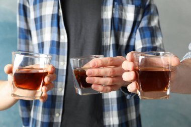 Men drink, cheers. Glasses of whiskey against blue background, c