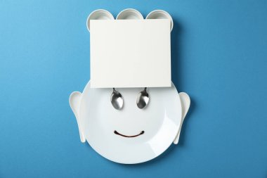Chef face made of cutlery and tableware on blue background, spac