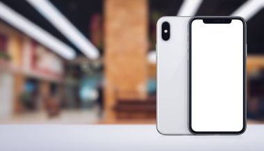 Smartphone similar to iPhone X mockup front and back sides on the desk in office space banner with copy space