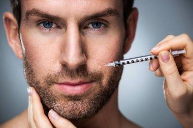 Man during surgery filling facial wrinkles