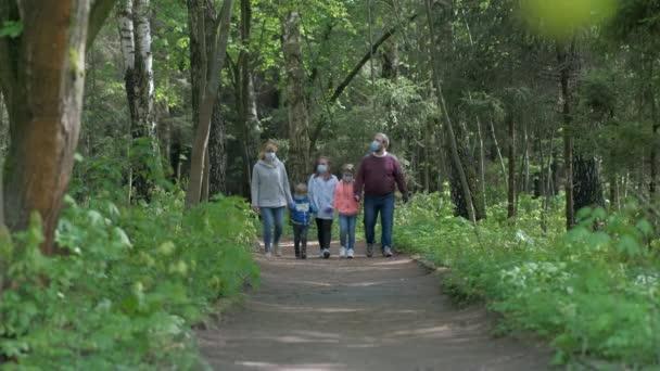 Rodina: otec, matka, syn a dvě dcery chodí na jaře do parku v lékařských maskách. Koncept ochrany před covid-19 koronavirovými infekcemi.