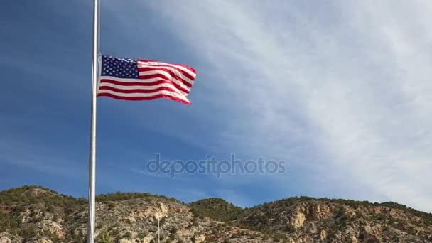 Americká vlajka na půl žerdi, vlající ve větru