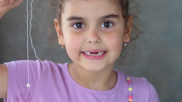 Portrét usměvavého bezzubého dítěte držícího zub na provázku. Úspěšný pokus o odstranění zubu. Vytáhni ten zub nití. Odstranit zub doma.