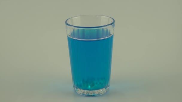 modrá tekutina ve sklenici s ledem na bílém pozadí
