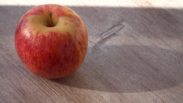 ripe apple on a wooden background. sun shadow falls on the fruit