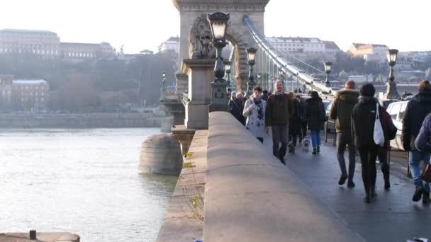 lidé jdou přes most