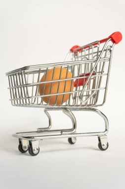 toy little consumer food trolley from steel with red plastic handle on a gray background with one fresh egg inside. empty space