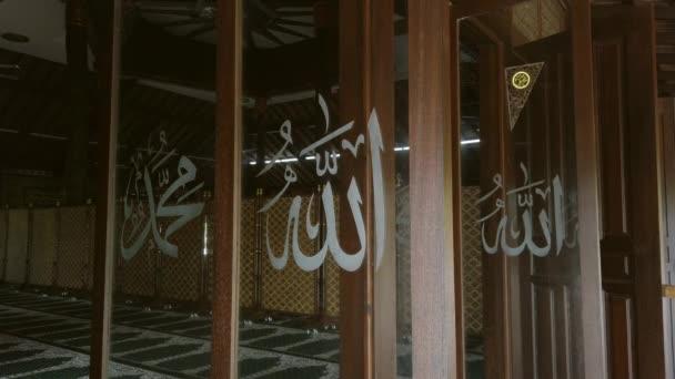 Statische Ansicht von Allah und dem Propheten Muhammad (a.s.) in arabischen Schriftzeichen, die auf das rotierende Glasfenster vor einer Moschee geschrieben sind.