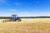 Starý traktor v poli v seně