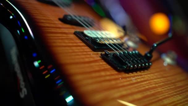 Detailní záběr: elektrická kytara, struny a hnědé dřevěné tělo, makro fotografie, umělé osvětlení
