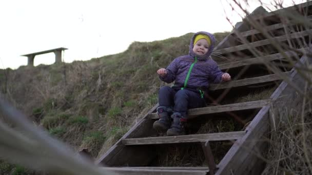 A small boy in a demi-season jacket and jeans sits on wooden steps on the slope of the river Bank in the evening, he says something, stamps his feet and looks at the camera