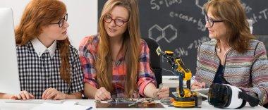 Students and professor building a robotic arm