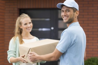 Happy courier delivering a package