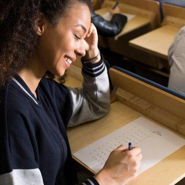 Happy student writing easy exam