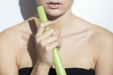 Young woman holding a leek