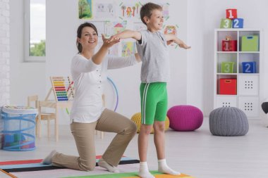 Physiotherapist exercising with a school-boy