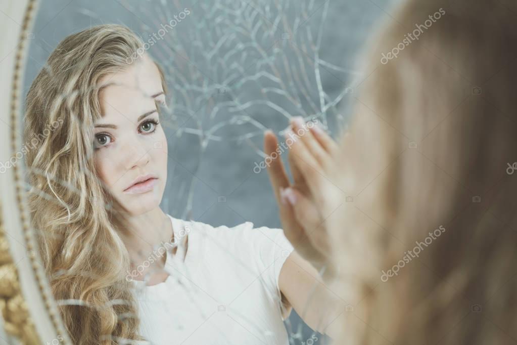 Woman reflection in broken mirror