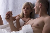 Naked couple smoking in bed
