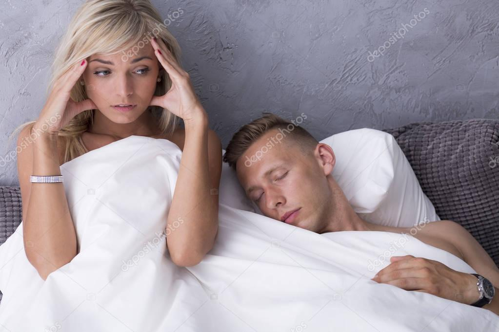 Scared woman in bed with lover