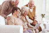 Skupina seniorů pomocí přenosného počítače