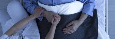 Nurse holding older man's hand