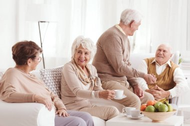 Seniors talking and drinking coffee