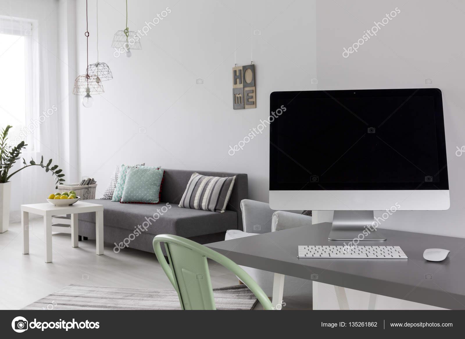 Grijs bureau met computer in moderne woonkamer u stockfoto