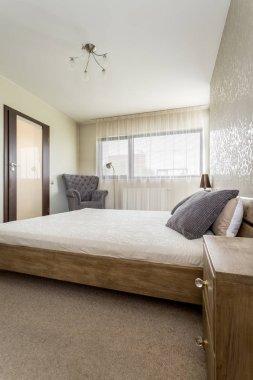 Wooden bed, nightstand in bedroom