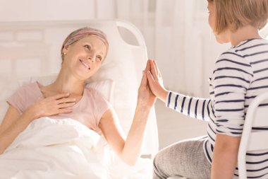 Cancer woman touching child's hand