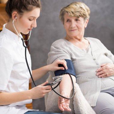 Nurse taking elderly woman's blood pressure