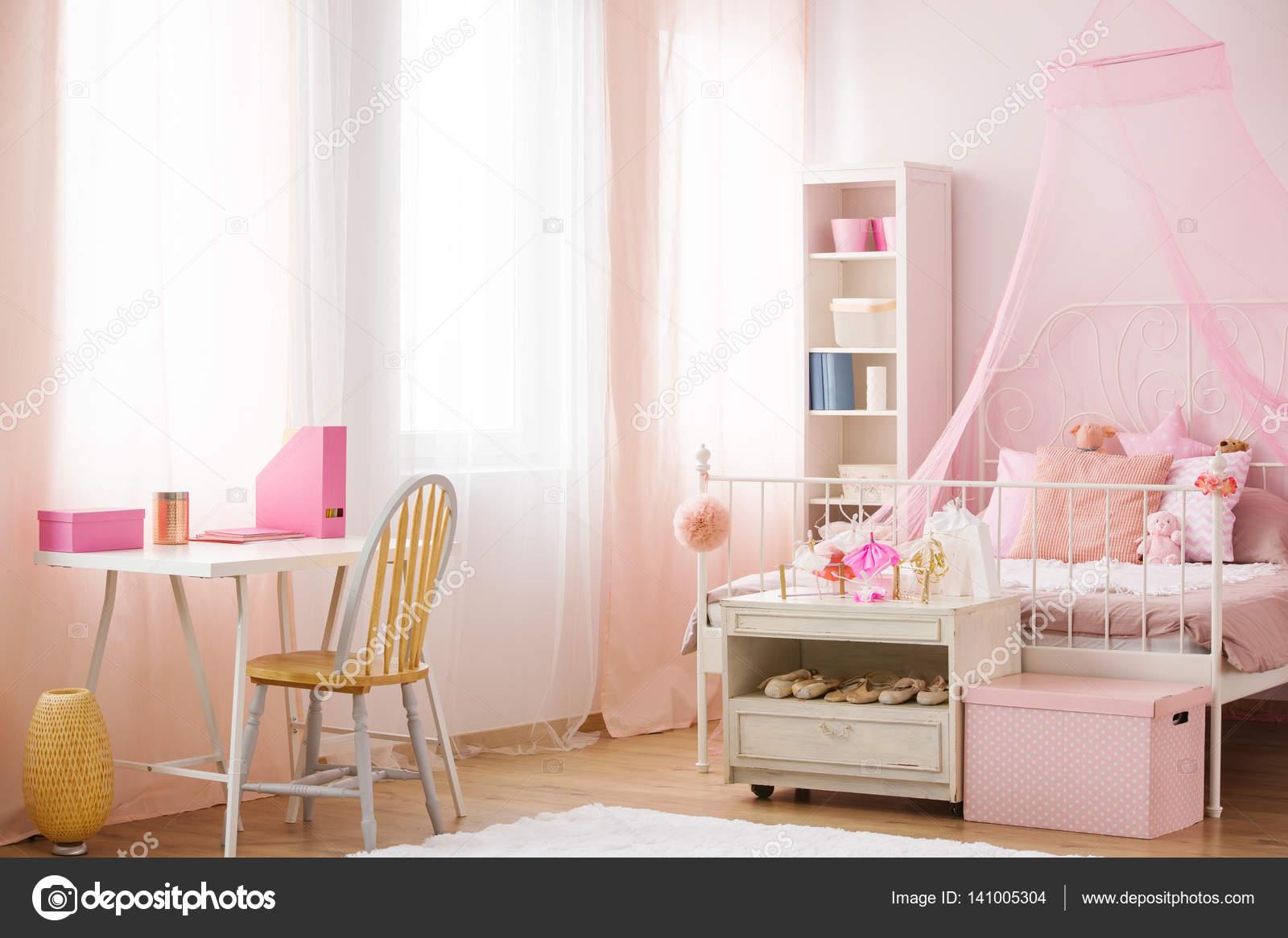 de slaapkamer van het kind met roze hemelbed stoel en balie foto van photographeeeu