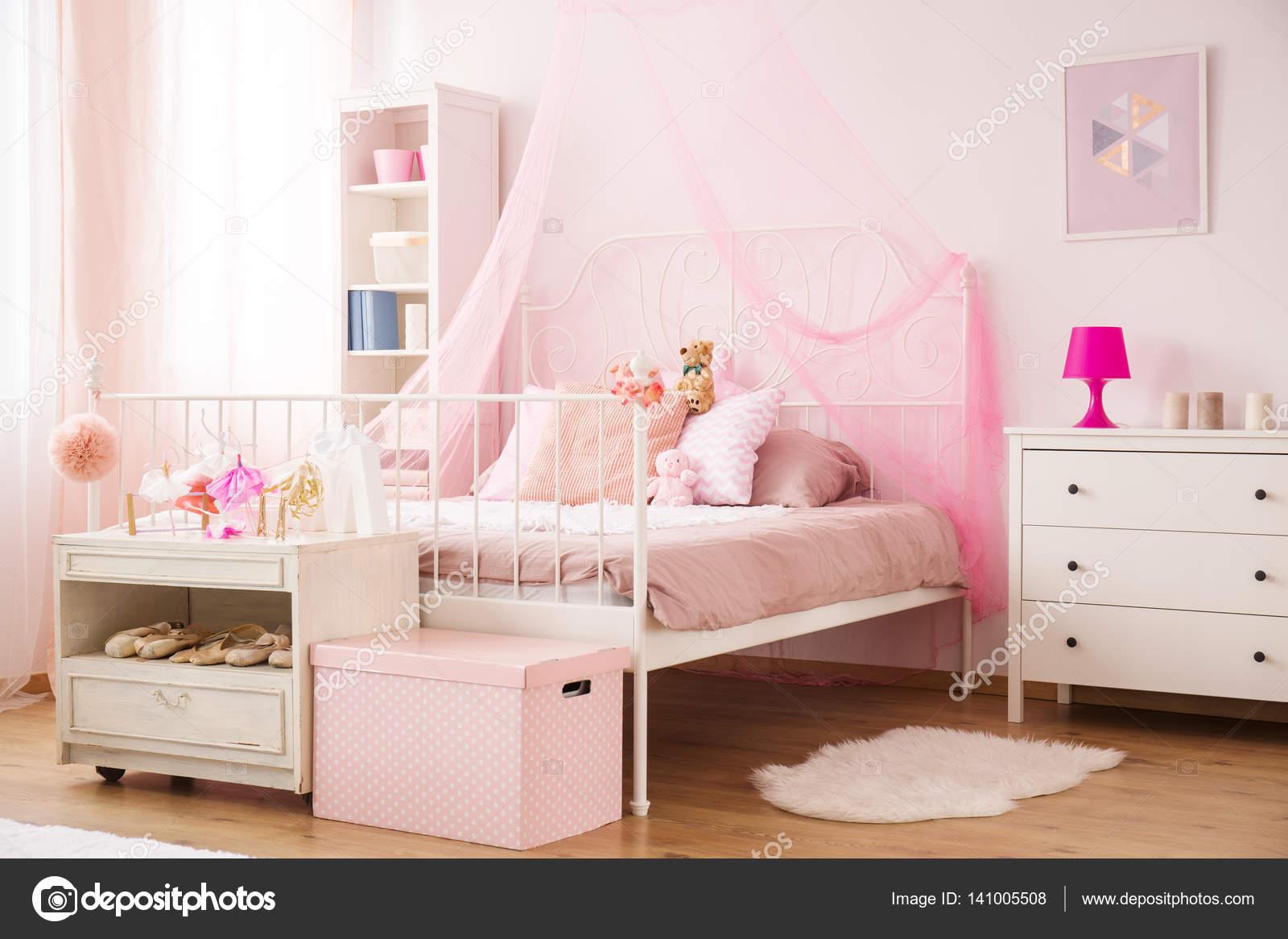 gezellige kind slaapkamer in roze met hemelbed en dressoir foto van photographeeeu