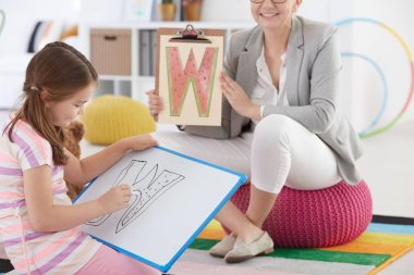 Therapist and girl drawing letter