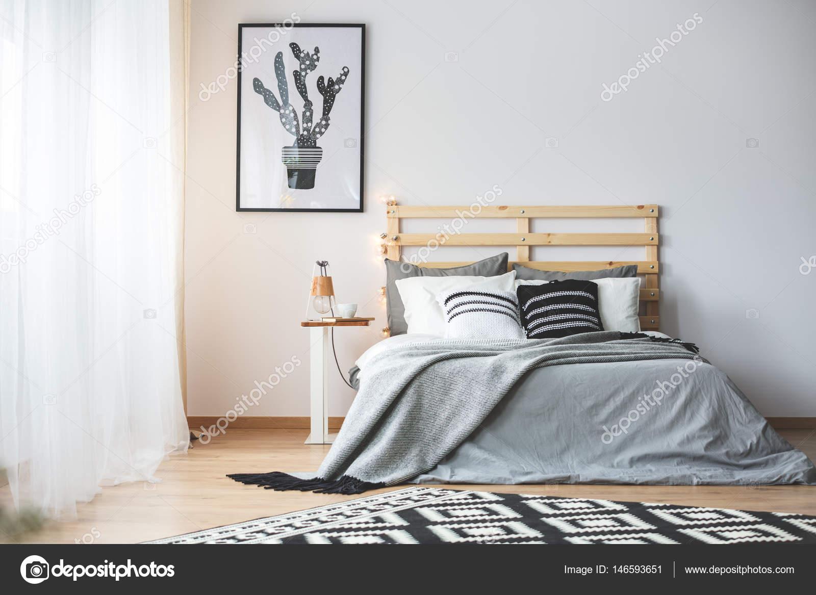 zwart wit slaapkamer met grijs accessoires groot venster en cactus poster foto van photographeeeu