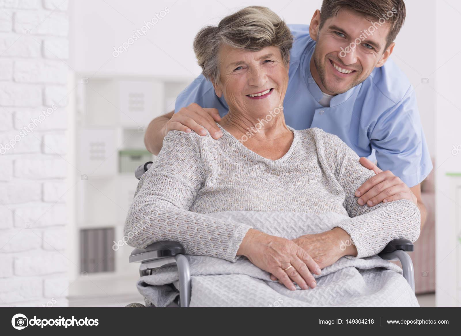 Asistente de mayores cuidados con alegre mujer con discapacidad en ancianos  — Foto de photographee.eu