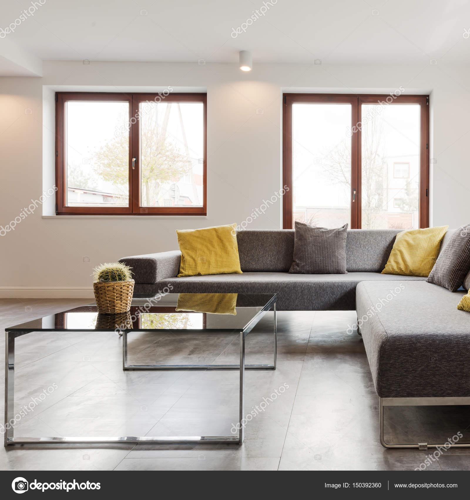 grote hoek bank en glazen salontafel in een zeer modern en licht huis interieur foto van photographeeeu